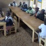Vorschulkinder mit neuen Stühlen und Bänken